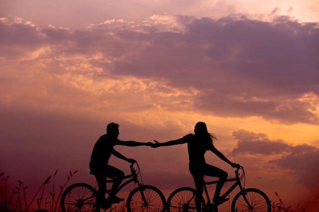 夕暮れに自転車に乗る人の画像