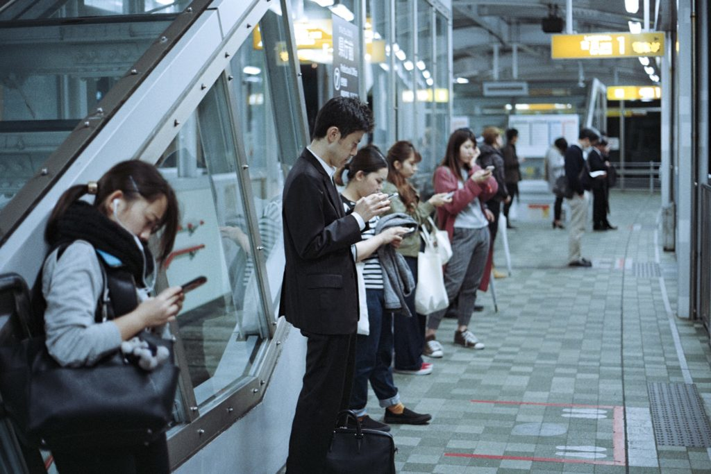 電車を待っている社会人の画像
